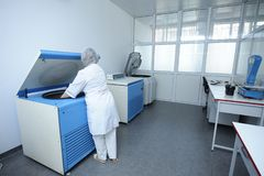 Enfermera que coloca los envases con sangre en una centrifugadora fotografía de archivo