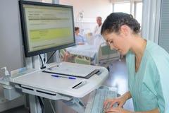 Enfermera que comprueba la pantalla del hospital imagen de archivo libre de regalías