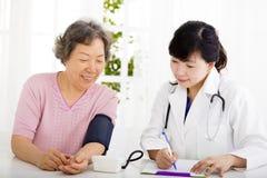 Enfermera que comprueba la presión arterial de la mujer mayor Imagenes de archivo