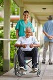 Enfermera que conduce al hombre mayor Imágenes de archivo libres de regalías