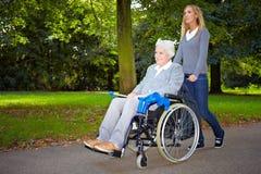 Enfermera que conduce a la mujer mayor Imagen de archivo