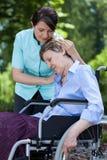 Enfermera que conforta a una mujer mayor en la silla de ruedas Imagen de archivo libre de regalías