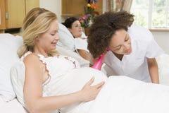 Enfermera que controla el vientre y la sonrisa de la mujer embarazada Imágenes de archivo libres de regalías
