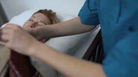 Enfermera que cuida que cubre al viejo paciente femenino durmiente con la manta, rehabilitación del hospital almacen de video