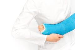 Enfermera que cuida que toma cuidado de la pierna quebrada del muchacho Imágenes de archivo libres de regalías