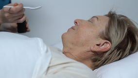 Enfermera que da el jarabe al paciente femenino mayor que miente en la cama, tratamiento hospitalario almacen de metraje de vídeo