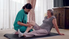 Enfermera que da masaje de la pierna a la mujer mayor en una casa de retiro almacen de video
