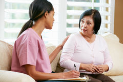 Enfermera que discute expedientes con el paciente femenino mayor Imagen de archivo