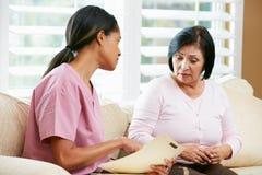 Enfermera que discute expedientes con el paciente femenino mayor durante hogar Foto de archivo libre de regalías