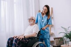 Enfermera que empuja la silla de ruedas fotografía de archivo libre de regalías