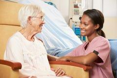Enfermera que habla con el paciente femenino mayor asentado en silla Imagen de archivo