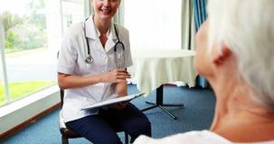Enfermera que habla con una mujer mayor paciente metrajes