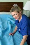 Enfermera que hace la cama de hospital Fotografía de archivo