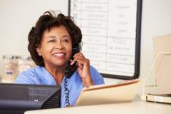 Enfermera que hace llamada de teléfono en la estación de las enfermeras Imagen de archivo libre de regalías