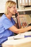 Enfermera que hace llamada de teléfono en la estación de las enfermeras Foto de archivo libre de regalías