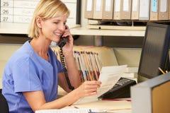 Enfermera que hace llamada de teléfono en la estación de las enfermeras Fotos de archivo