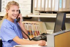 Enfermera que hace llamada de teléfono en la estación de las enfermeras Imagenes de archivo