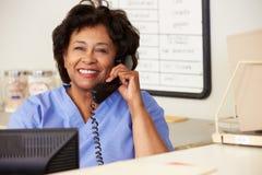 Enfermera que hace llamada de teléfono en la estación de las enfermeras Foto de archivo