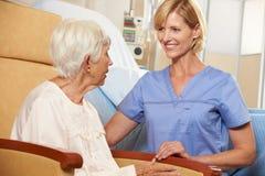 Enfermera que lleva el paciente femenino mayor asentado en silla Imagenes de archivo