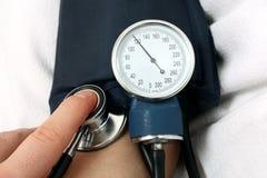 Enfermera que mide la presión arterial Foto de archivo