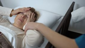 Enfermera que pone la compresa en la frente femenina de los pacientes en el hospital, atención sanitaria almacen de metraje de vídeo