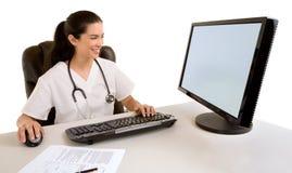 Enfermera que se sienta y que trabaja en su ordenador Foto de archivo libre de regalías