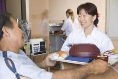 Enfermera que sirve a un paciente una comida en su cama imagen de archivo