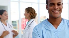 Enfermera que sonríe y que se coloca delante del equipo médico almacen de metraje de vídeo
