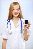 Enfermera que sostiene un teléfono móvil disponible Fotos de archivo