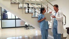 Enfermera que sostiene una libreta en las escaleras almacen de metraje de vídeo