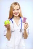 Enfermera que sostiene una manzana y píldoras Imagen de archivo libre de regalías