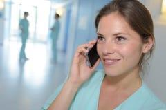Enfermera que tiene conversación sobre el teléfono móvil fotos de archivo