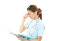 Enfermera que tiene un dolor de cabeza Foto de archivo