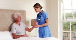 Enfermera que toma el pulso de su paciente metrajes