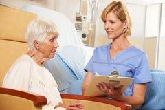 Enfermera que toma notas del paciente femenino mayor asentado en silla Imágenes de archivo libres de regalías