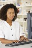 Enfermera que trabaja en el ordenador en farmacia Fotos de archivo libres de regalías