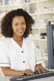 Enfermera que trabaja en el ordenador en farmacia Imagenes de archivo