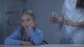 Enfermera que trae el agua y píldoras a la niña enferma que mira a través de ventana lluviosa almacen de metraje de vídeo
