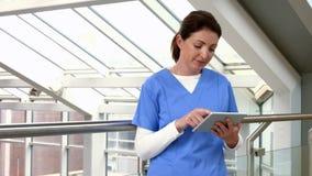 Enfermera que usa la PC de la tableta en vestíbulo metrajes
