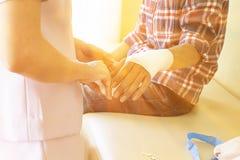 Enfermera que venda la mano del paciente masculino Imágenes de archivo libres de regalías
