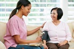 Enfermera que visita al paciente femenino mayor en casa fotos de archivo