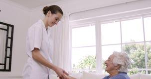 Enfermera sonriente que ayuda a la mujer mayor que hace ejercicios almacen de video