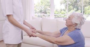 Enfermera sonriente que ayuda a la mujer mayor que hace ejercicios metrajes