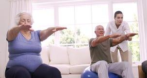 Enfermera sonriente que ayuda a los pares mayores que hacen ejercicios metrajes