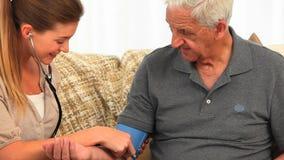 Enfermera sonriente que toma la presión arterial de su paciente masculino almacen de video