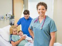 Enfermera Standing With Couple y bebé recién nacido adentro Imagen de archivo libre de regalías