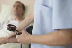 Enfermera Taking Blood Pressure y pulso del paciente Fotos de archivo