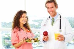 Enfermera y doctor con comida sana foto de archivo libre de regalías