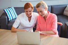 Enfermera y mujer mayor que usa un ordenador portátil Foto de archivo