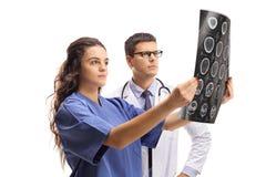 Enfermera y un doctor que examina una exploración de la radiografía fotos de archivo